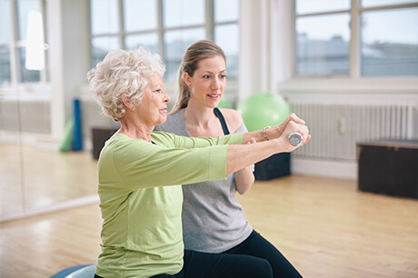 Activity coordinator exercising with senior resident