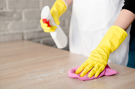 Gloved retirement housekeeping cleaning table